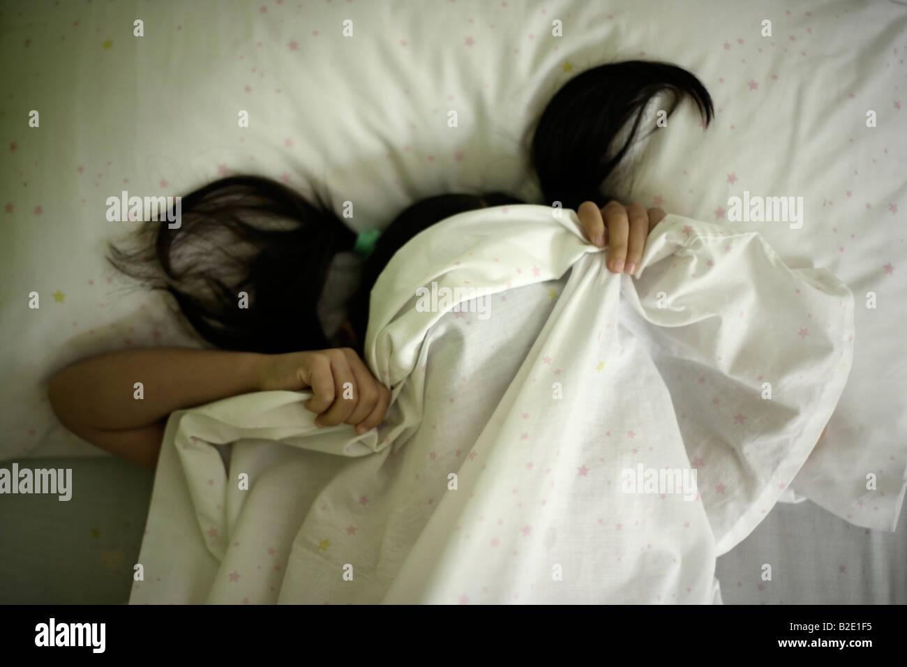 Bambina di cinque anni si nasconde sotto fogli dopo tantrum Immagini Stock