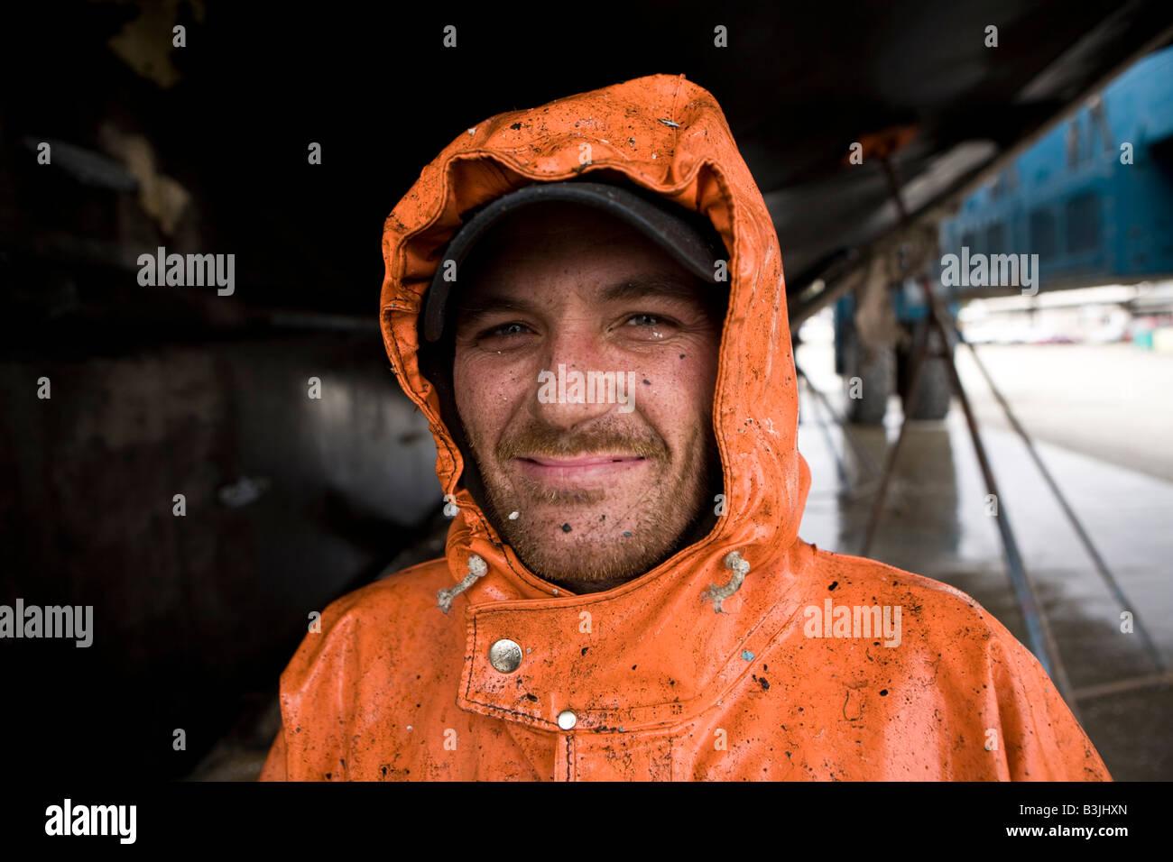 Robert Palmer lavaggi a pressione la parte inferiore di un 88 piedi lungo la pesca in barca Leann nel cantiere navale Immagini Stock