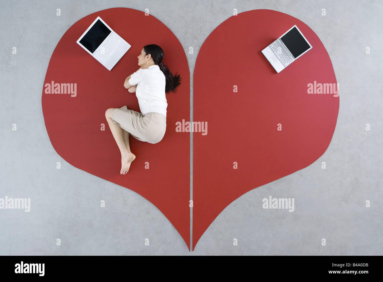 Donna giaceva a terra con il computer portatile sul grande cuore spezzato, laptop abbandonate dietro di lei Immagini Stock