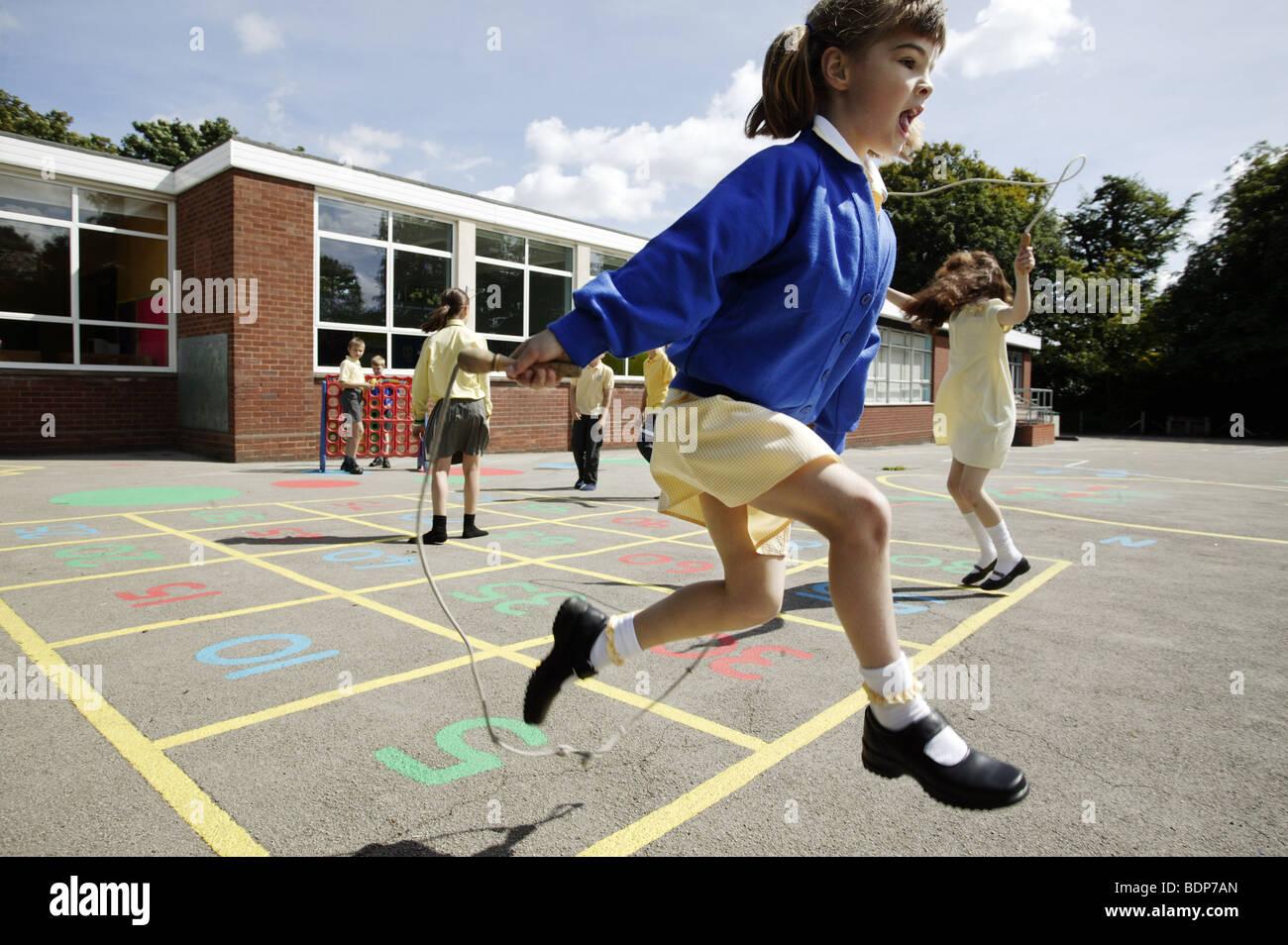 Studentesse saltando in una scuola primaria parco giochi nel Regno Unito. Immagini Stock
