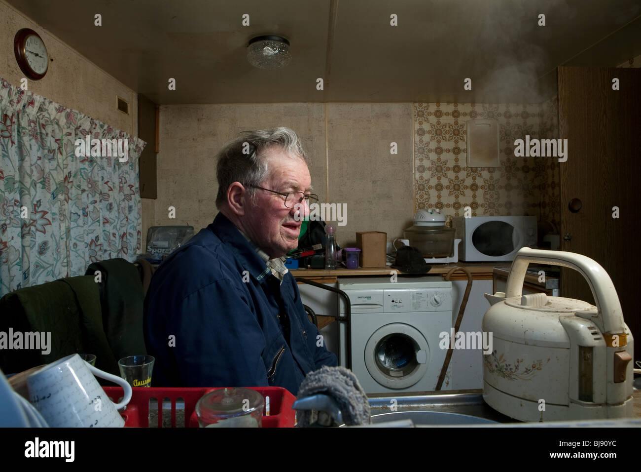 Senior singolo uomo guardando un bollitore bollire nella sua casa a motore Immagini Stock