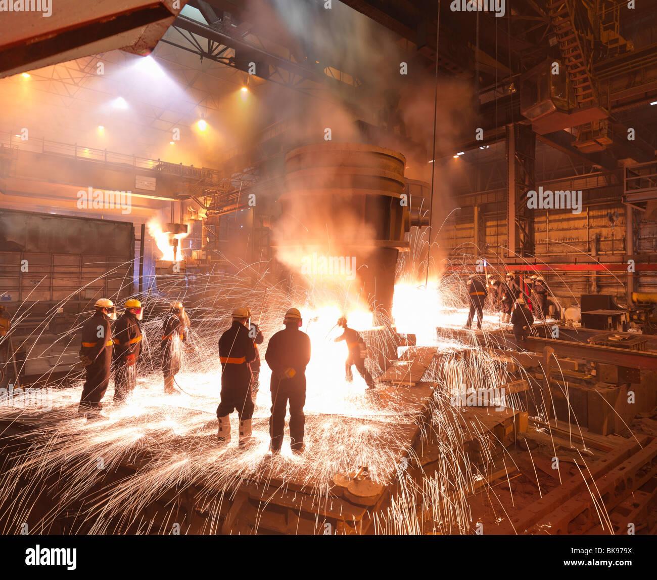 Lavoratori con acciaio fuso in una pianta Immagini Stock