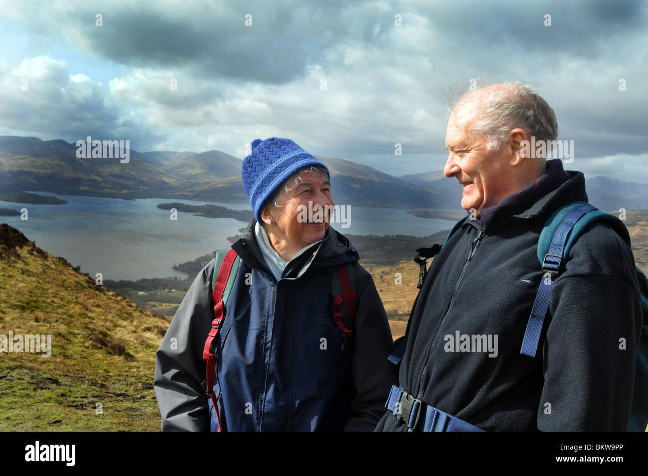 Persone anziane attive andare passeggiate in collina nel Trossachs National Park, Scozia Immagini Stock
