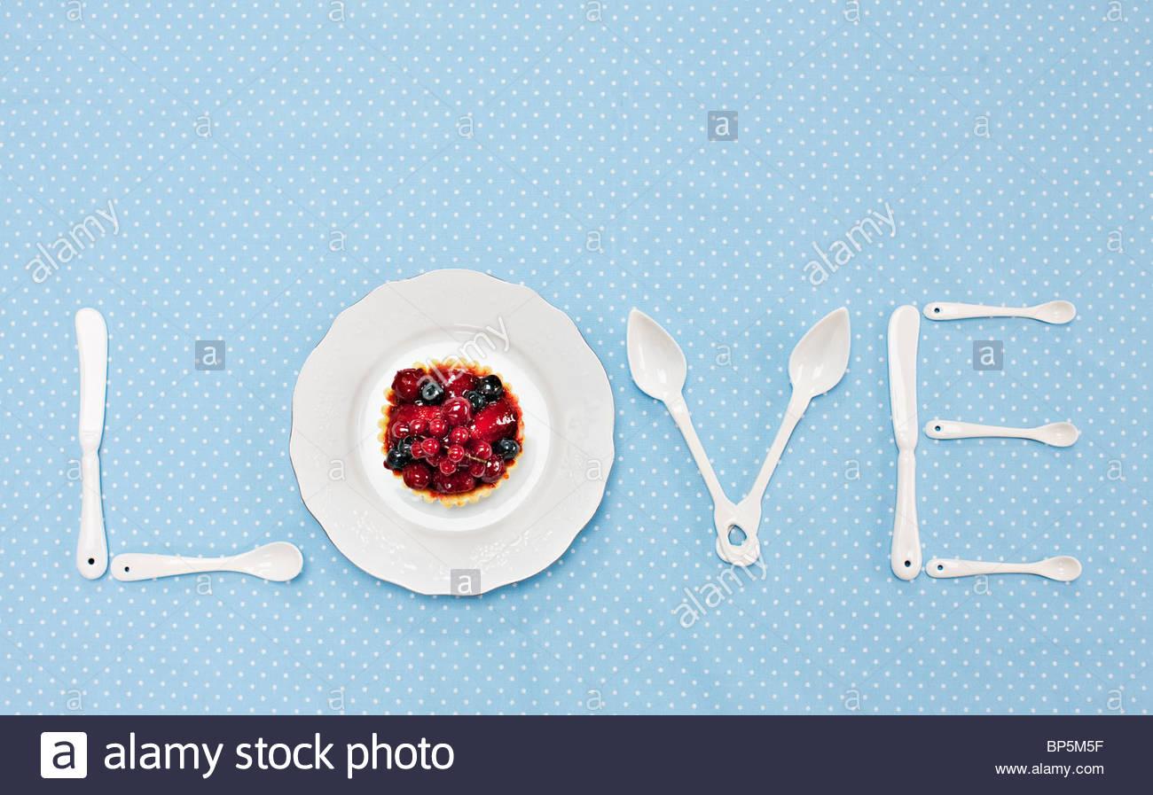 Argenteria e la piastra con tart ortografia 'amore' sulla tovaglia Immagini Stock
