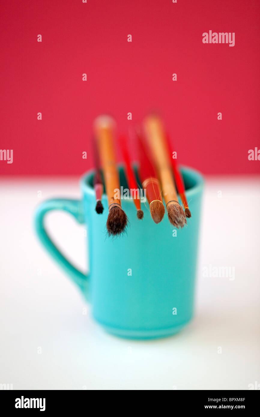 Artisti tazza da caffè con pennelli Immagini Stock