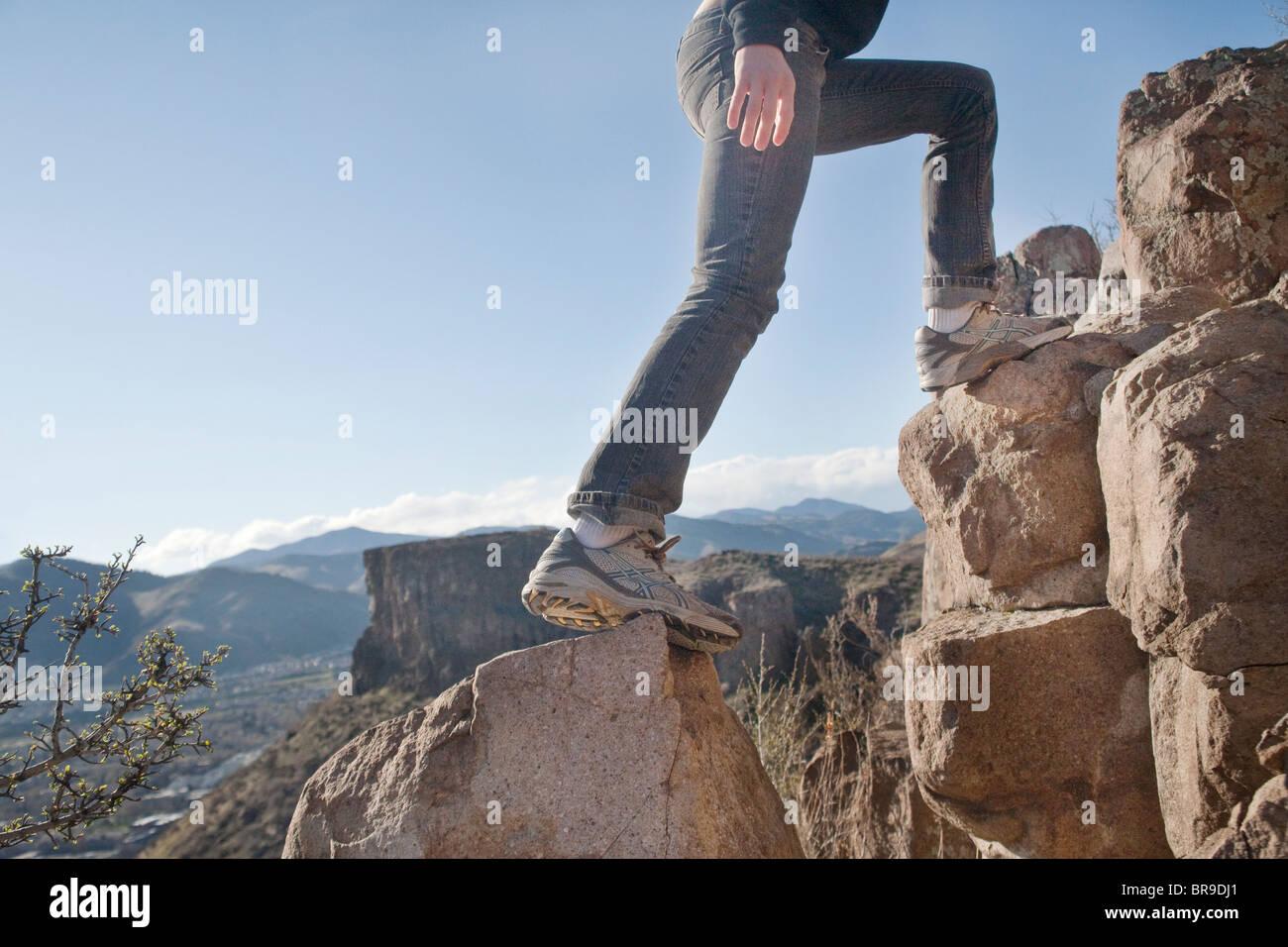 La donna si arrampica su rocce Immagini Stock