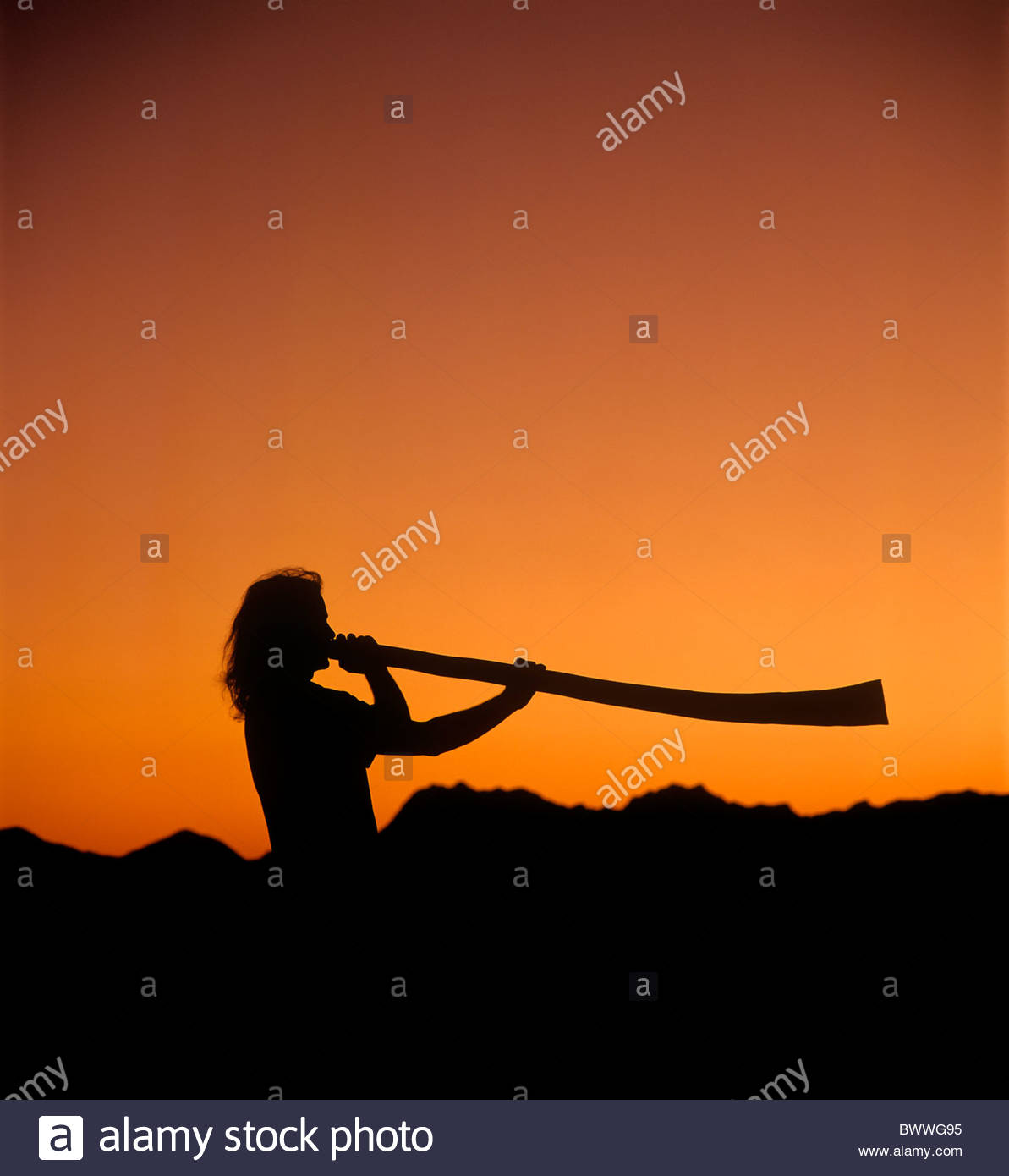 L'uomo gioca un didgeridoo al tramonto con le montagne di Tucson in silhouette di sfondo arancione e nero Immagini Stock
