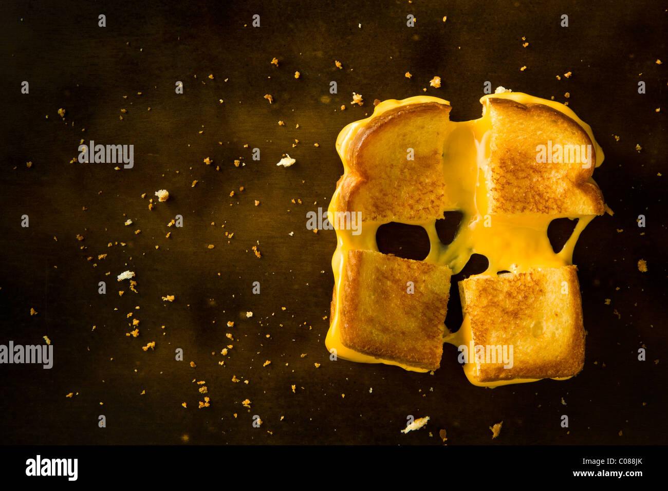 Un formaggio alla griglia panino tagliato in quattro piazze tirando il formaggio su una tavola di legno Immagini Stock