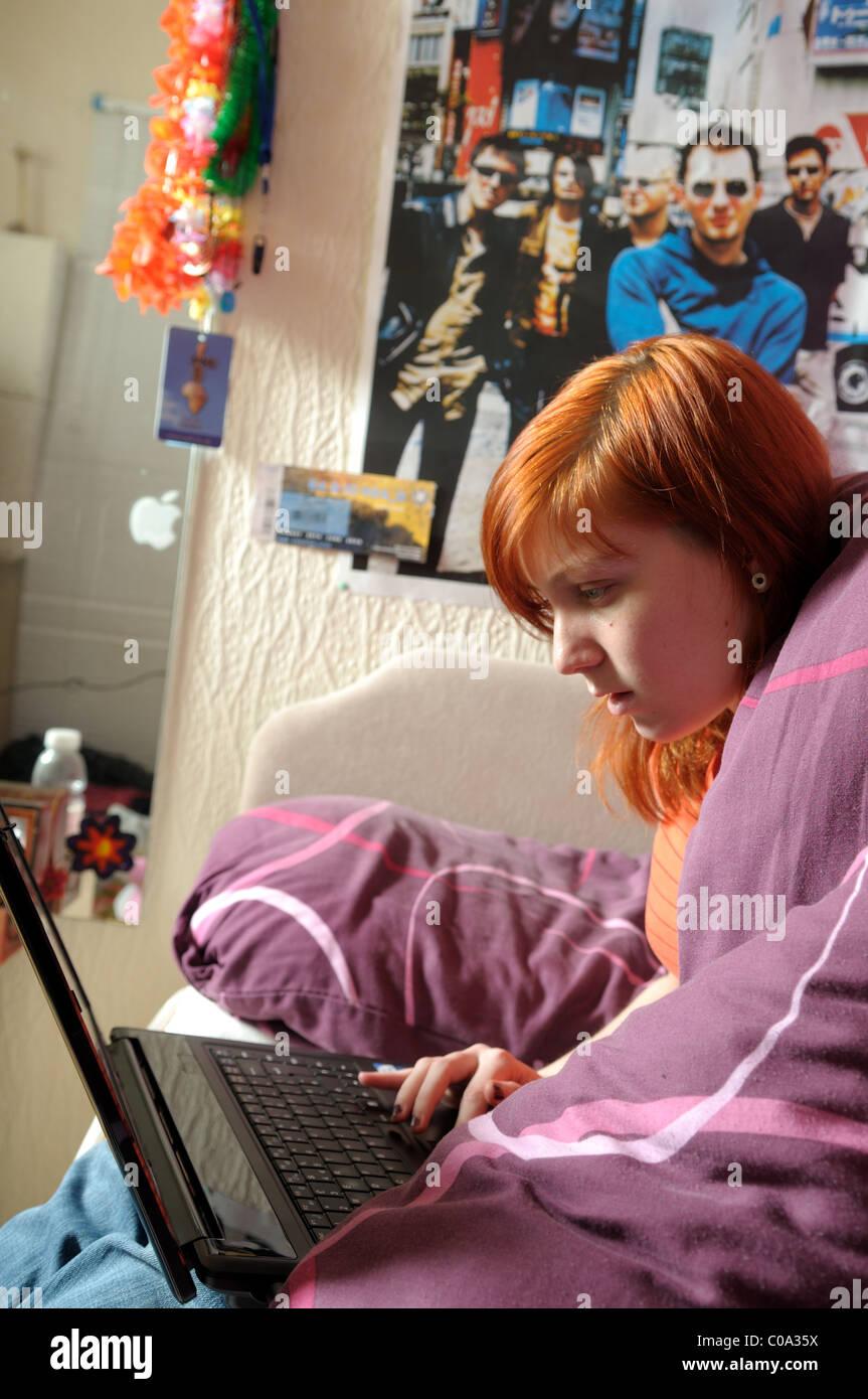 Giovani donne computer portatile in camera da letto. Immagini Stock