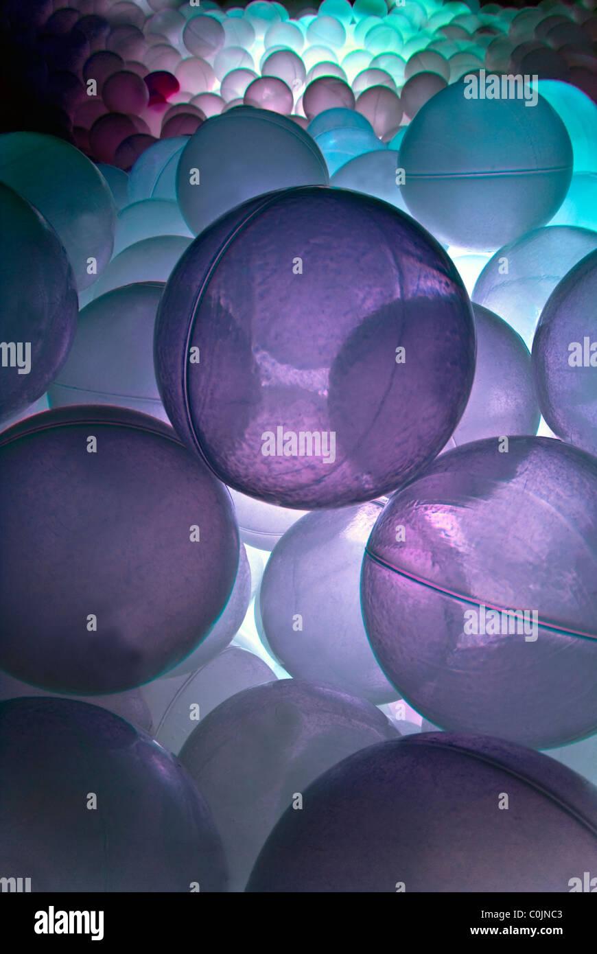 Piscina di palline con luce viola nella luminosa sala sensoriale. Immagini Stock