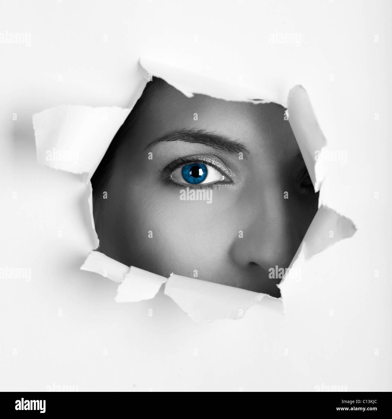 Bellissima femmina blue eye guardando attraverso un foro su un foglio di carta Immagini Stock