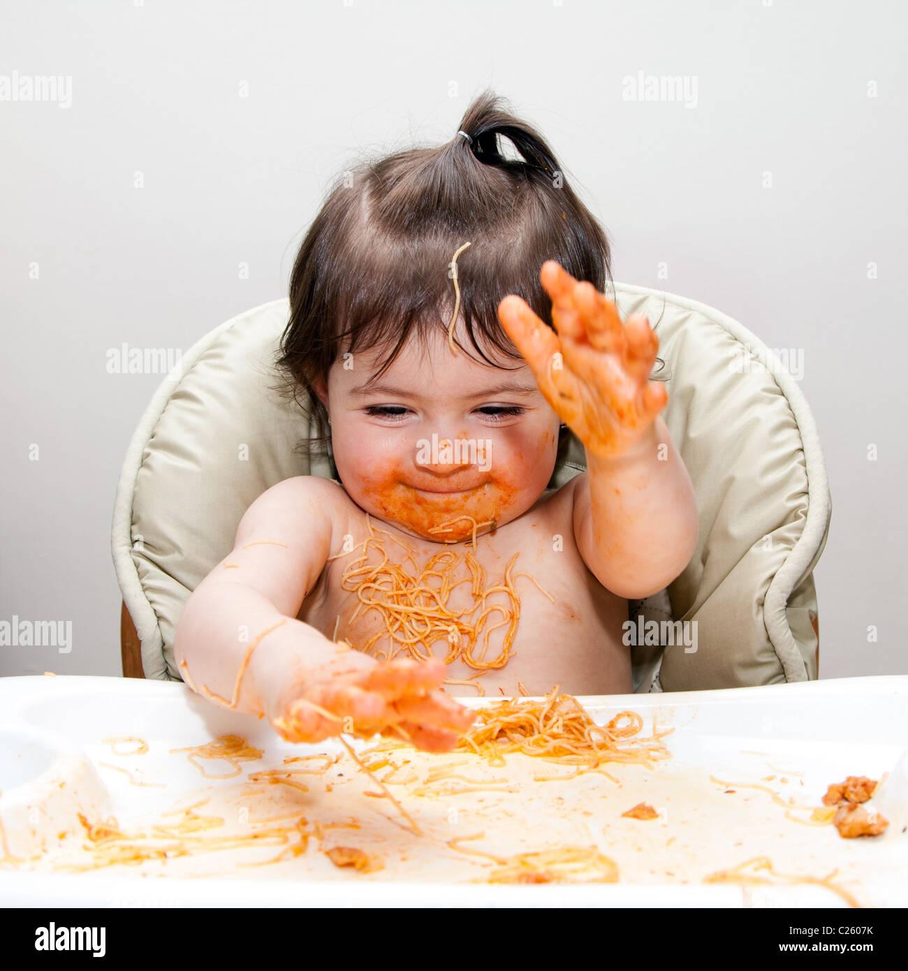 Happy baby divertirsi mangiando confuso slapping mani coperte in Spaghetti Angel Hair Pasta marinara rosso salsa Immagini Stock