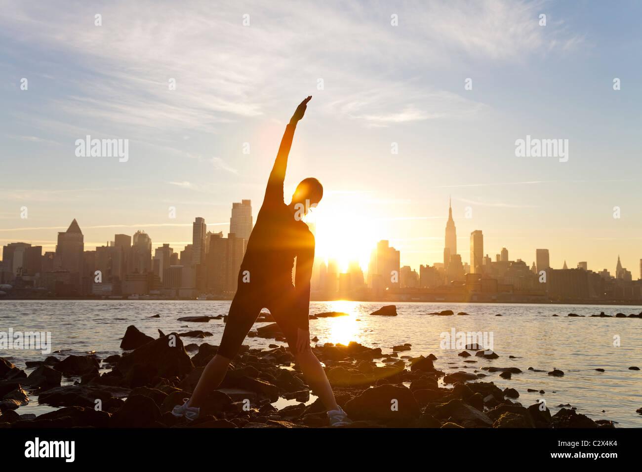 Una donna runner allungamento in una posizione di yoga nella parte anteriore dello skyline di Manhattan, New York Immagini Stock