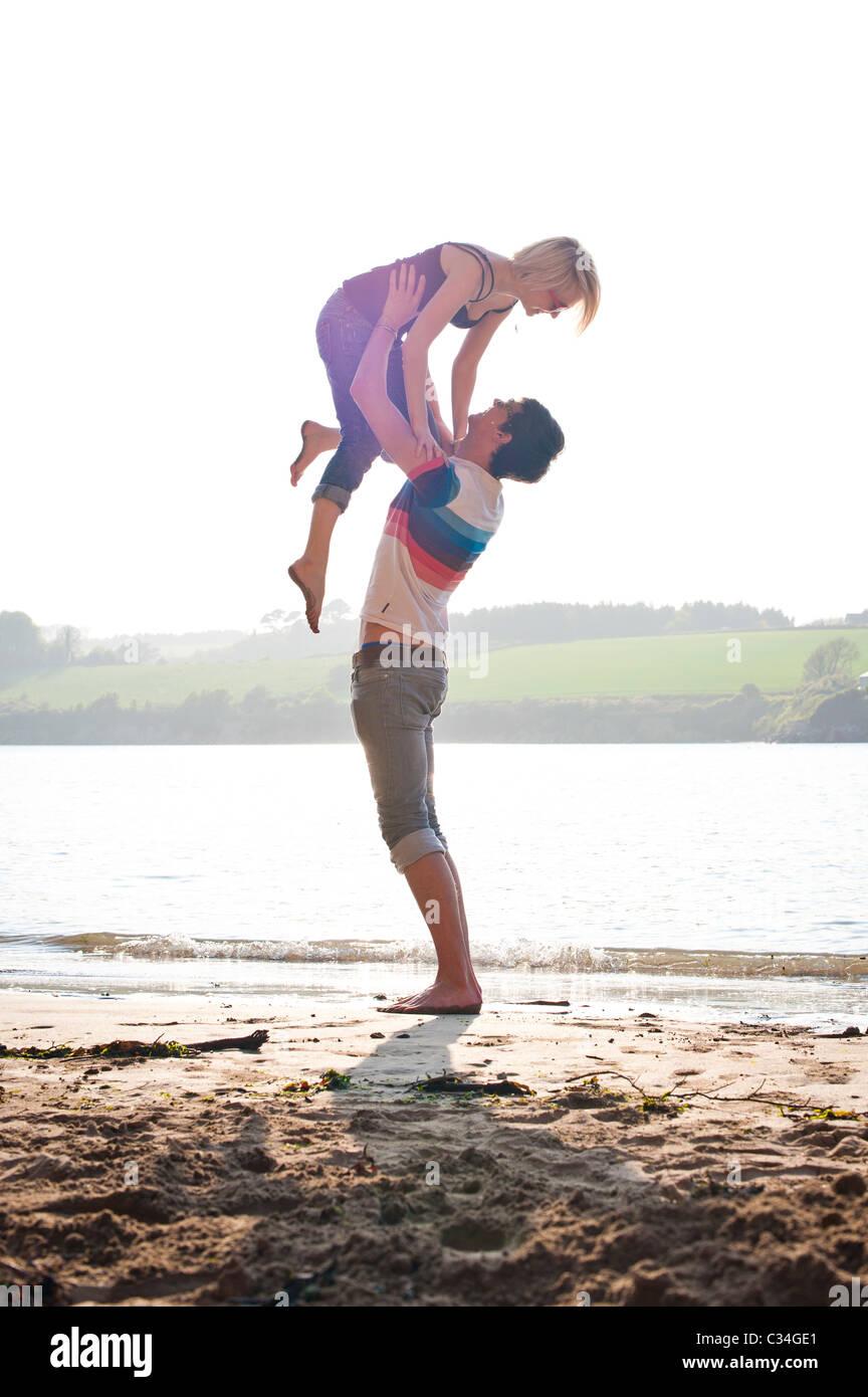 Uomo ragazza di sollevamento sulla spiaggia di estate, amare Immagini Stock