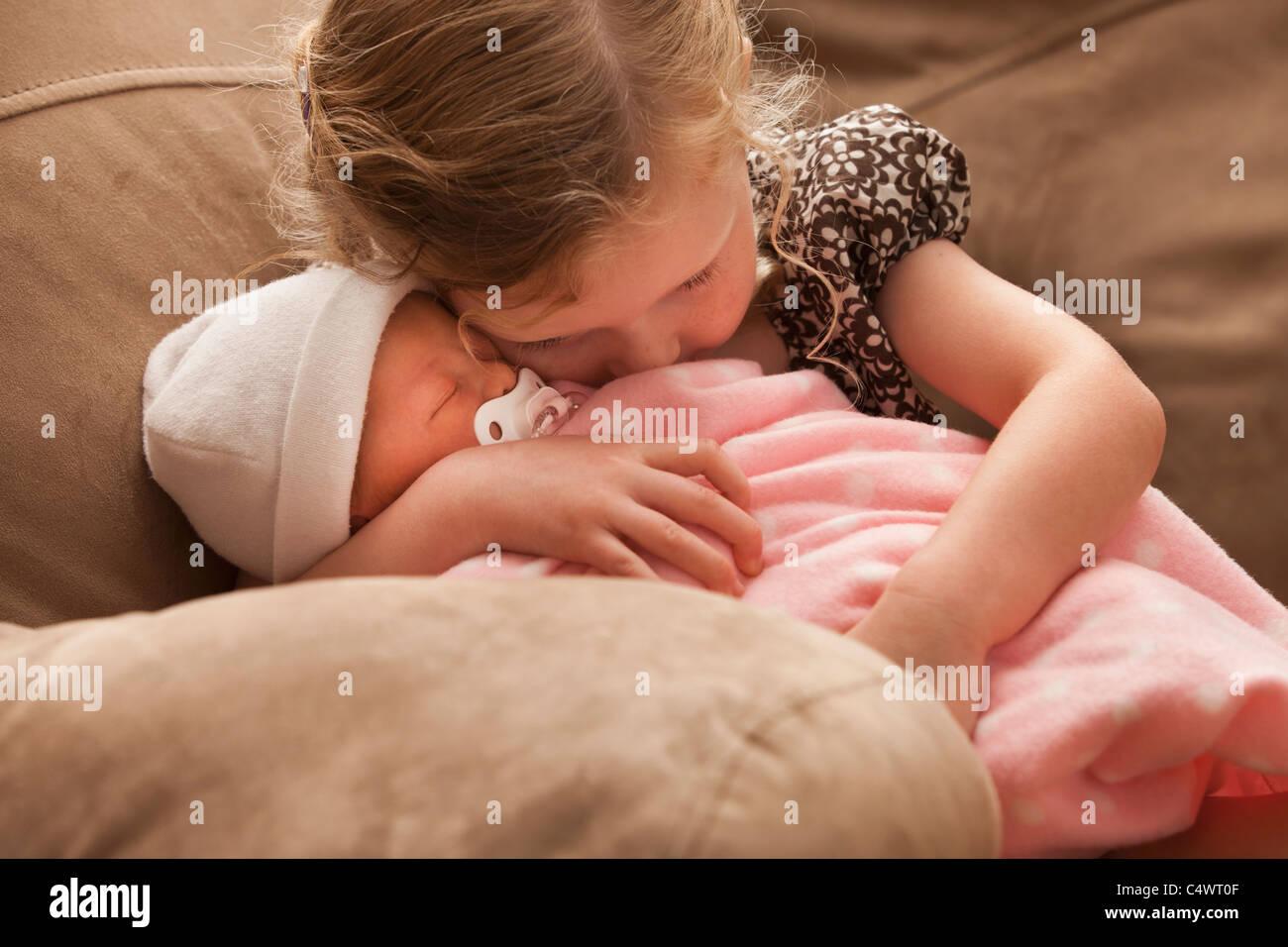 Stati Uniti d'America,Utah,Lehi,ragazza (2-3) abbracciando la sorella del bambino sul divano Immagini Stock