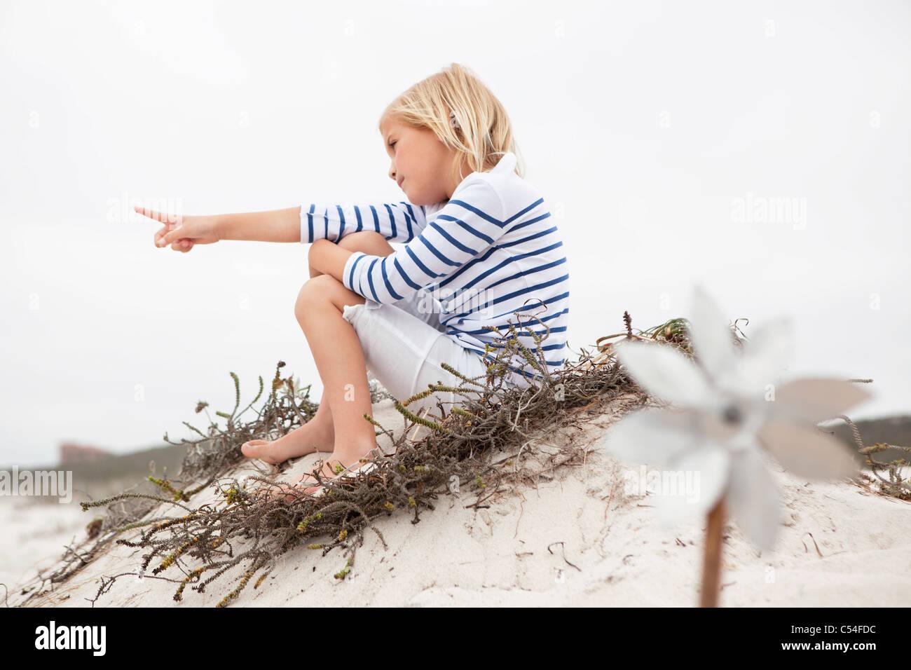 Messa a fuoco selettiva di una ragazza seduta sulla sabbia Immagini Stock