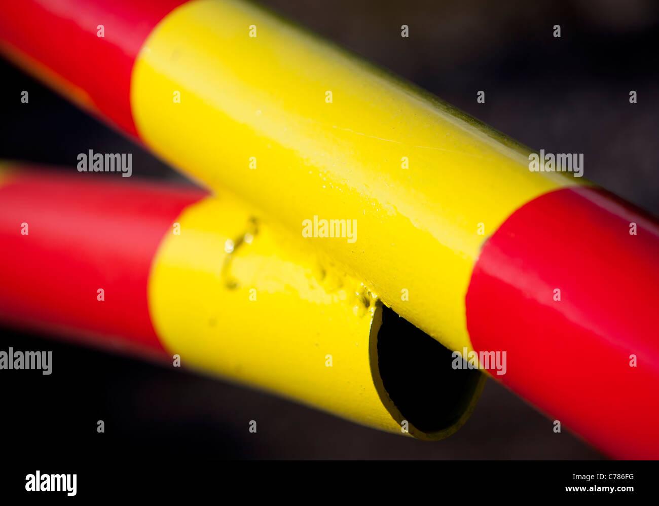 Primo piano di rosso e di giallo listati di braccio di metallo Immagini Stock