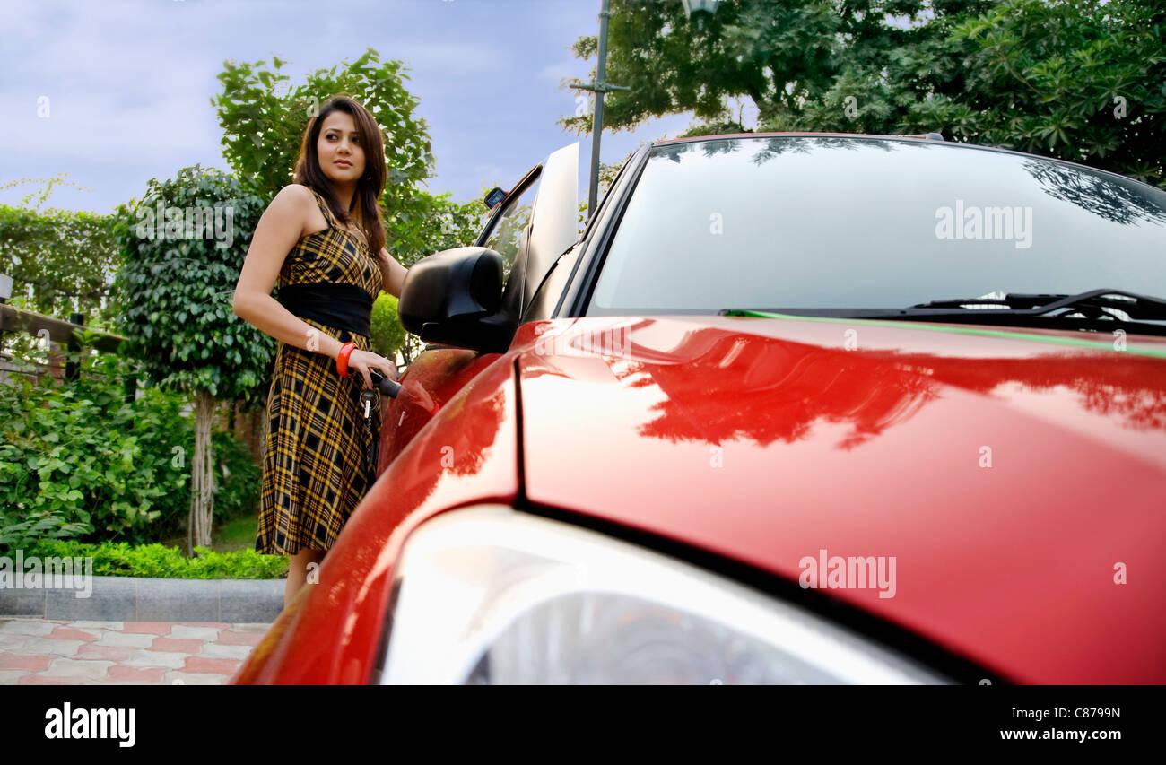Donna in piedi accanto a un auto Immagini Stock