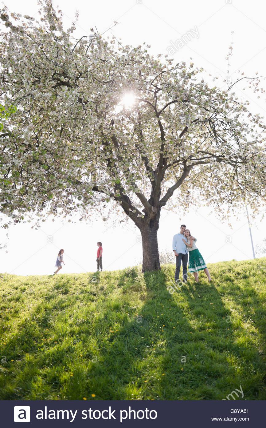 Famiglia giocare sotto agli alberi all'aperto Immagini Stock