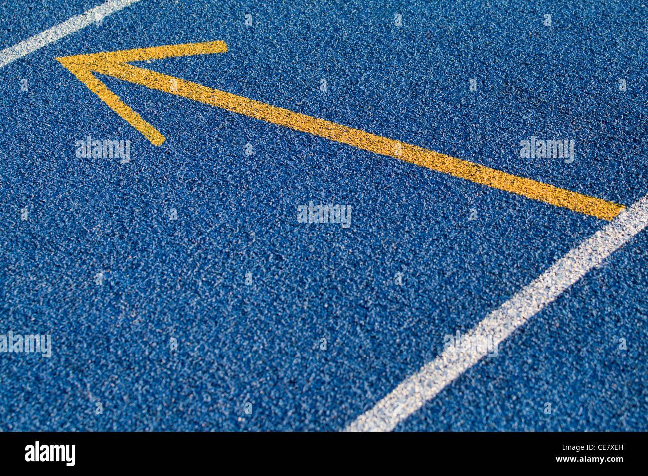 In tartan blu superficie con una freccia gialla Immagini Stock