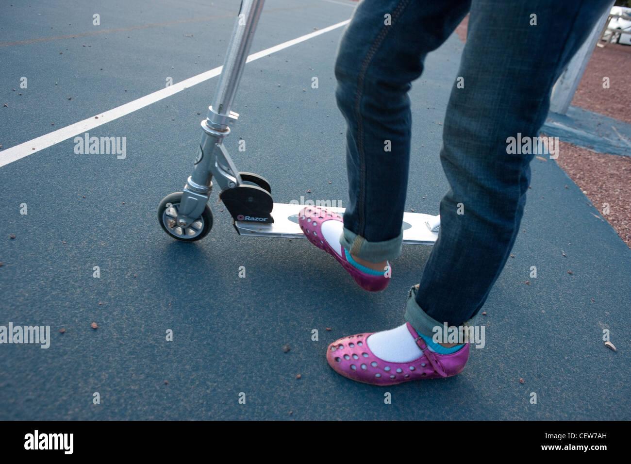 Ragazza che indossa sandali rosa a cavallo di un scooter Immagini Stock