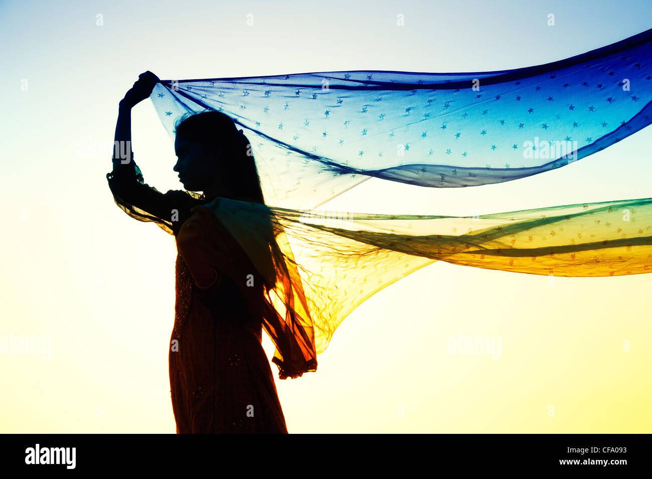 Ragazza indiana con star veli modellata dal vento. Silhouette Immagini Stock