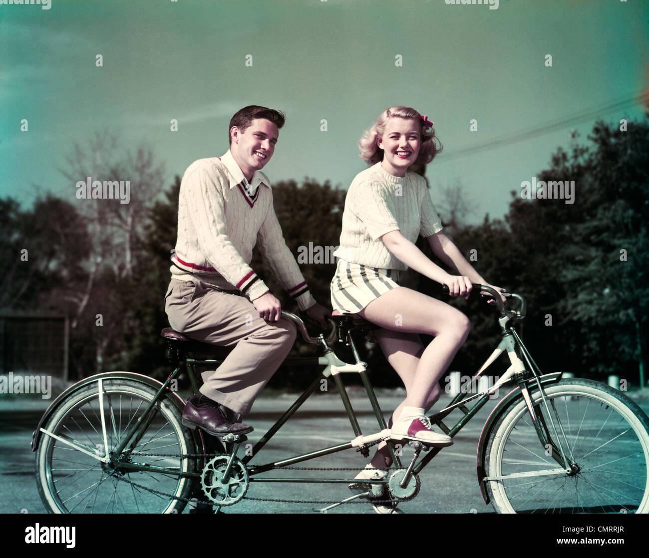 Anni Cinquanta sorridente giovane equitazione biciclette tandem costruita per due Immagini Stock