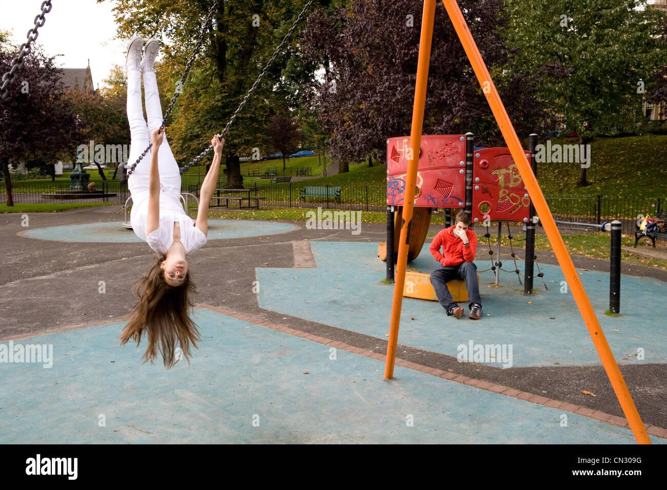Ragazza adolescente su altalena nel parco giochi, capovolto Immagini Stock