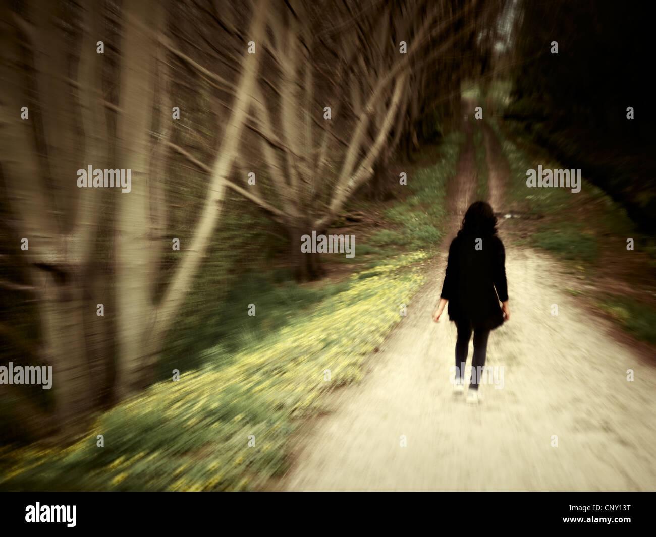 Donna cammina lungo via del bosco. Immagini Stock