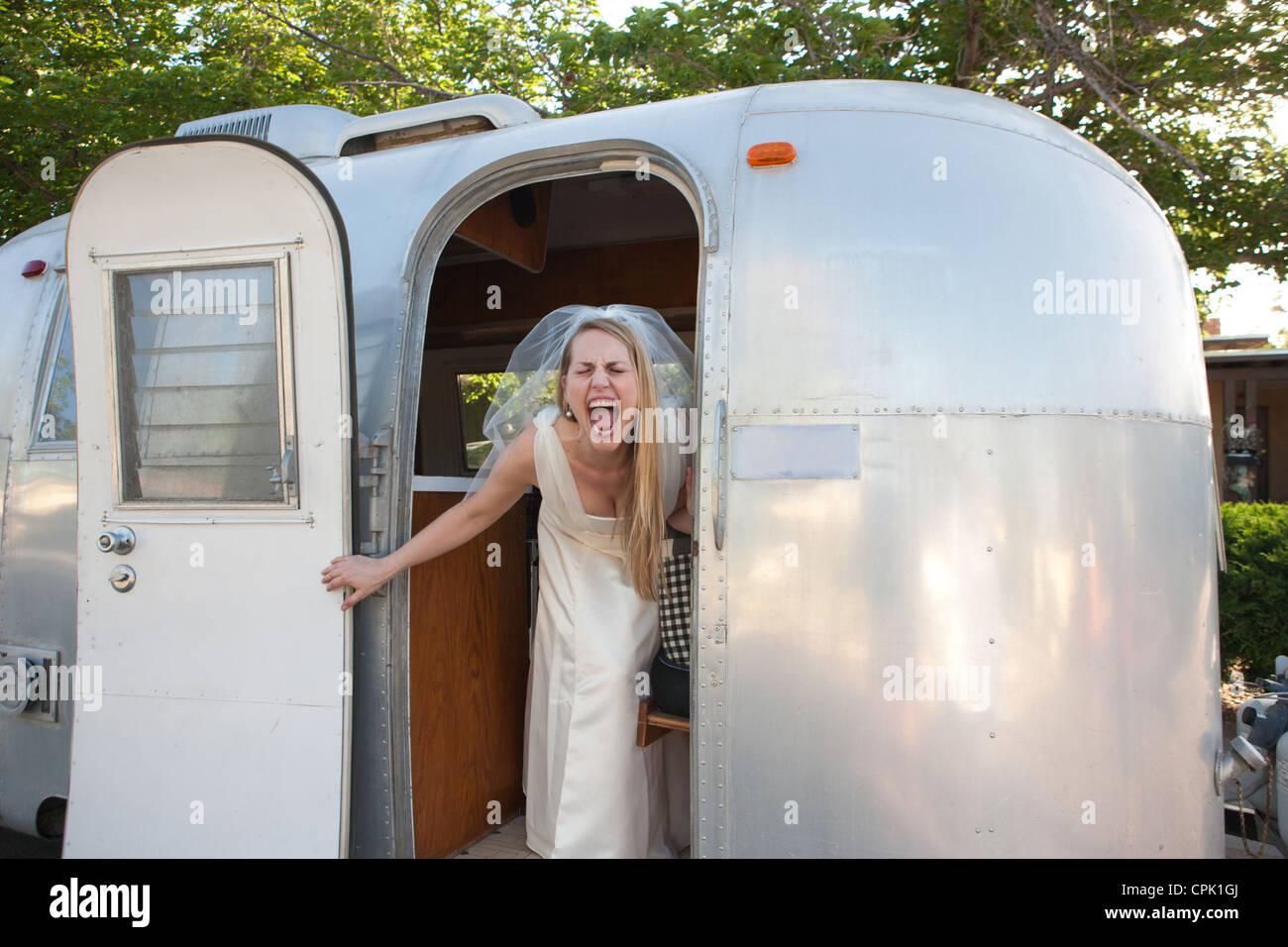 Sposa urlando con entusiasmo all'interno di un rimorchio Airstream. Immagini Stock