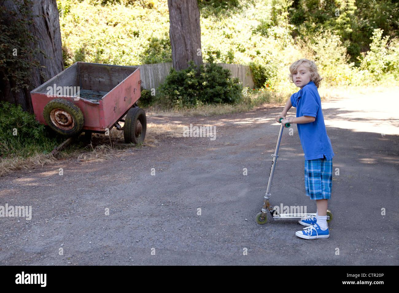 Ragazzo fuori a giocare sul suo scooter. Immagini Stock