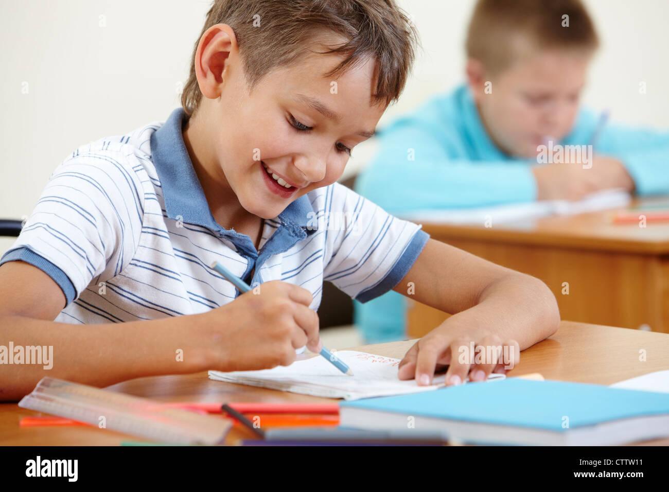 Ritratto di smart lad disegno a lezione con un compagno di classe sullo sfondo Immagini Stock