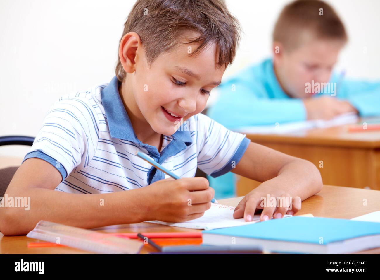 Ritratto di smart lad disegno a lezione con i compagni di classe su sfondo Immagini Stock
