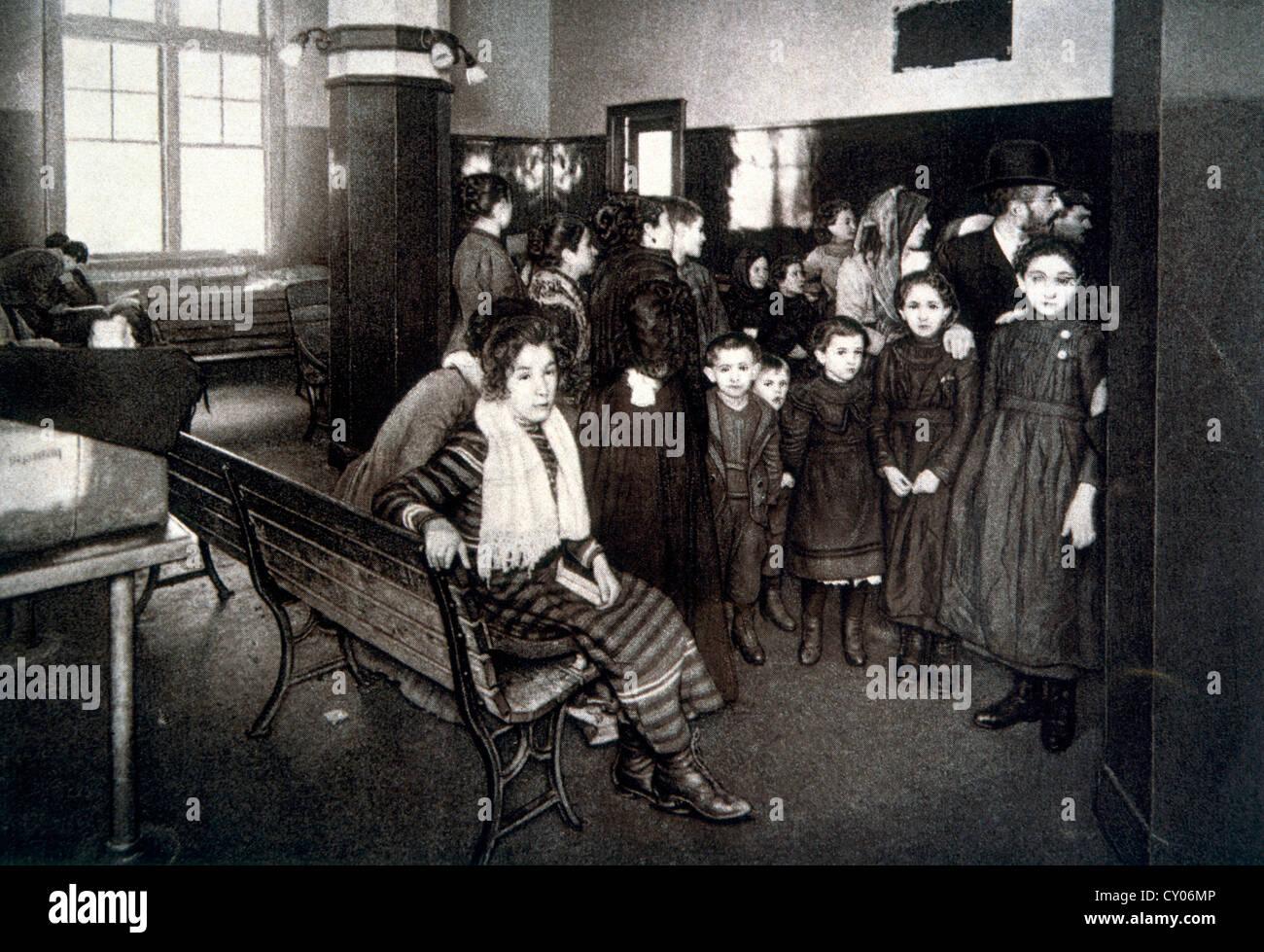 Gruppo di emigrati in attesa della penna di detenzione dopo il passaggio del loro esame di ammissione, Ellis Island, Immagini Stock