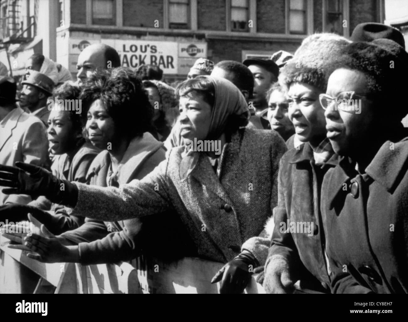 Sconvolto afro-americano di donne sventolare addio ucciso leader, Malcolm X, al tempio di fede, New York City, Stati Immagini Stock