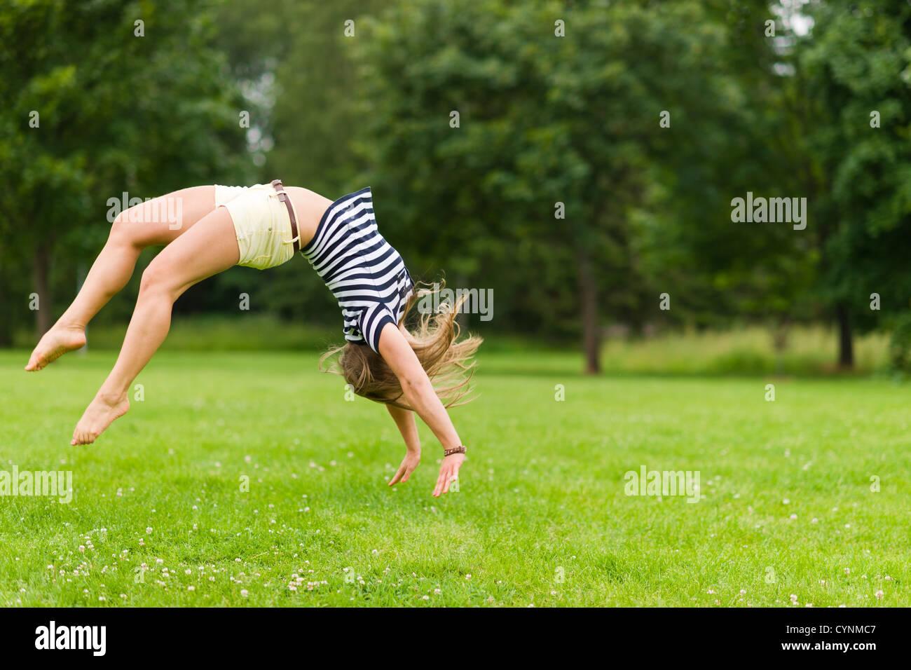 Giovane ragazza sportiva salta indietro al parco, immagine con profondità di campo ridotta Immagini Stock
