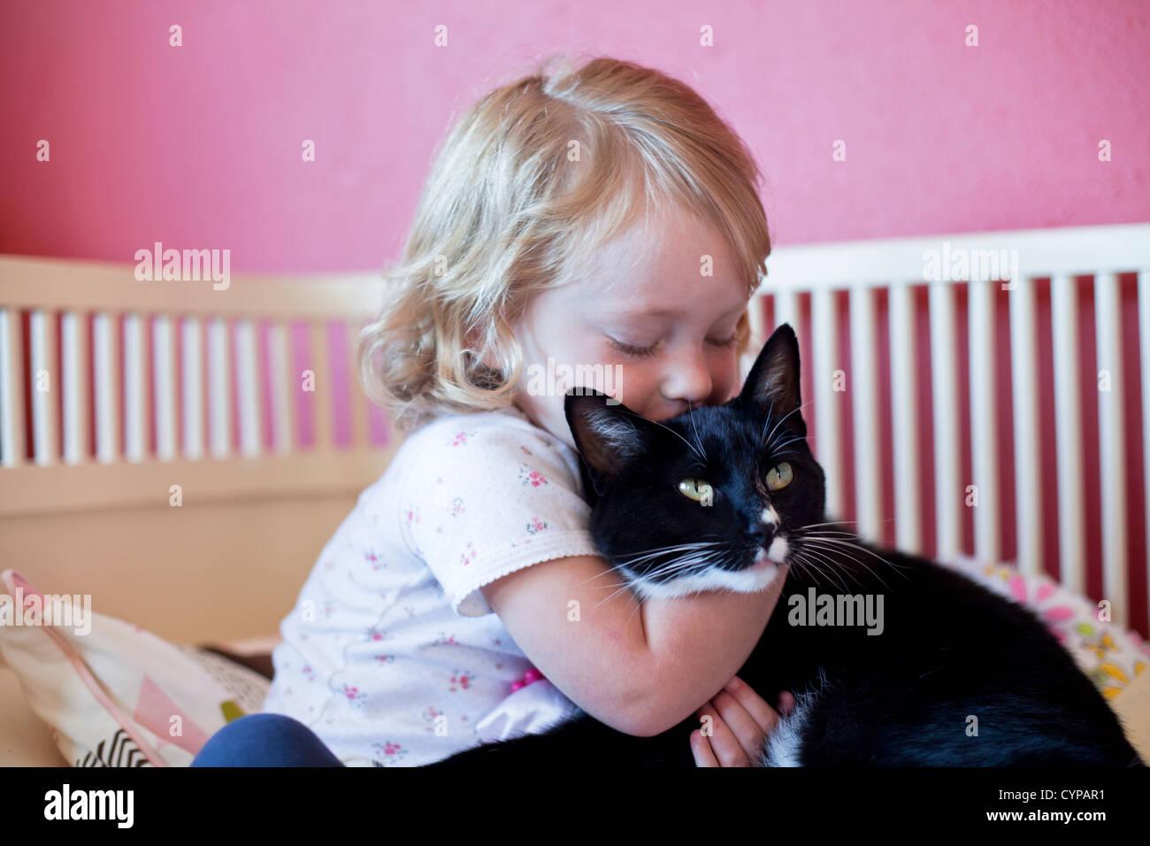 Il Toddler girl abbracciando il suo gatto. Immagini Stock