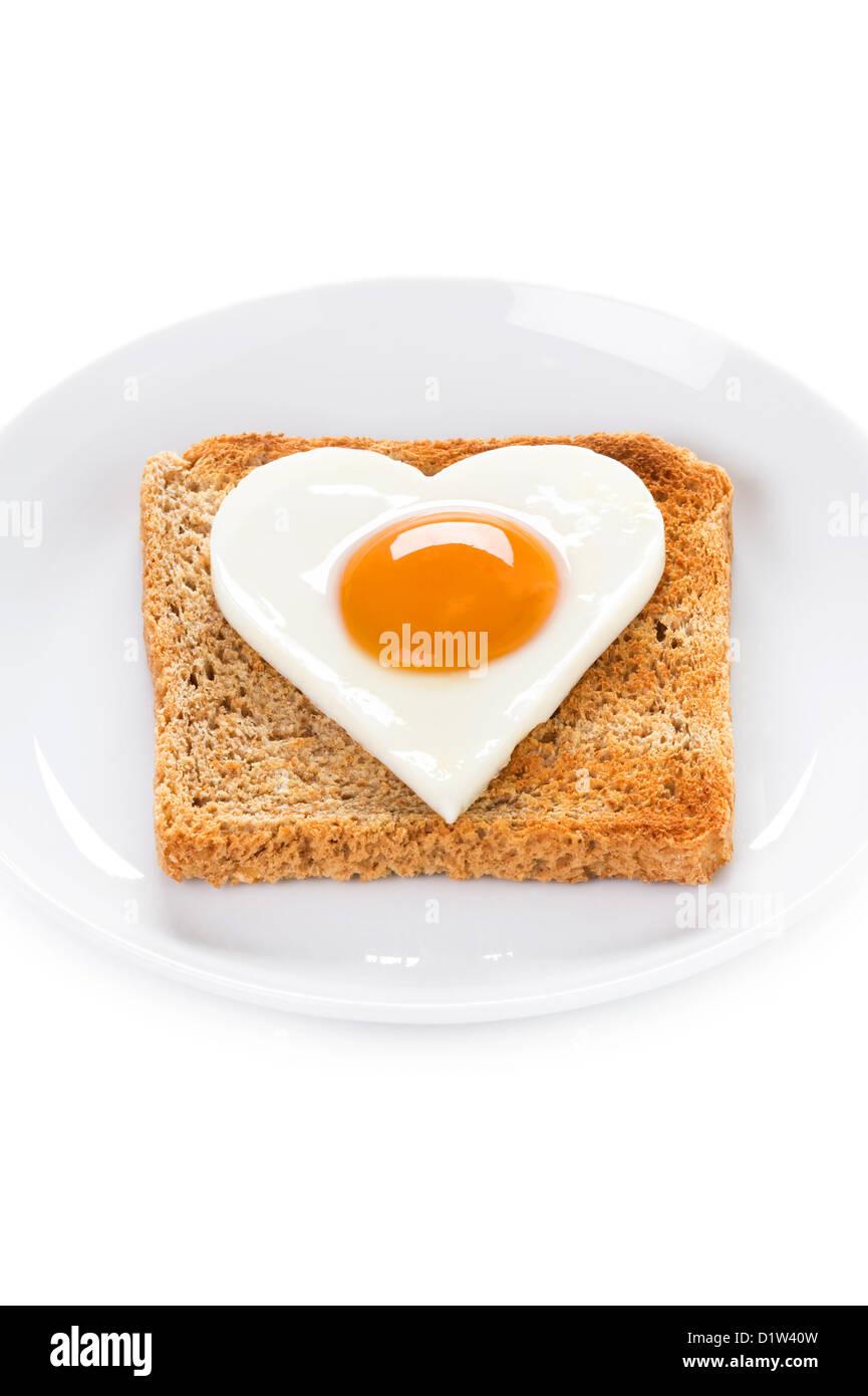 A forma di cuore di uova cotte su toast per illustrare il giorno di San Valentino la prima colazione o il colesterolo Immagini Stock