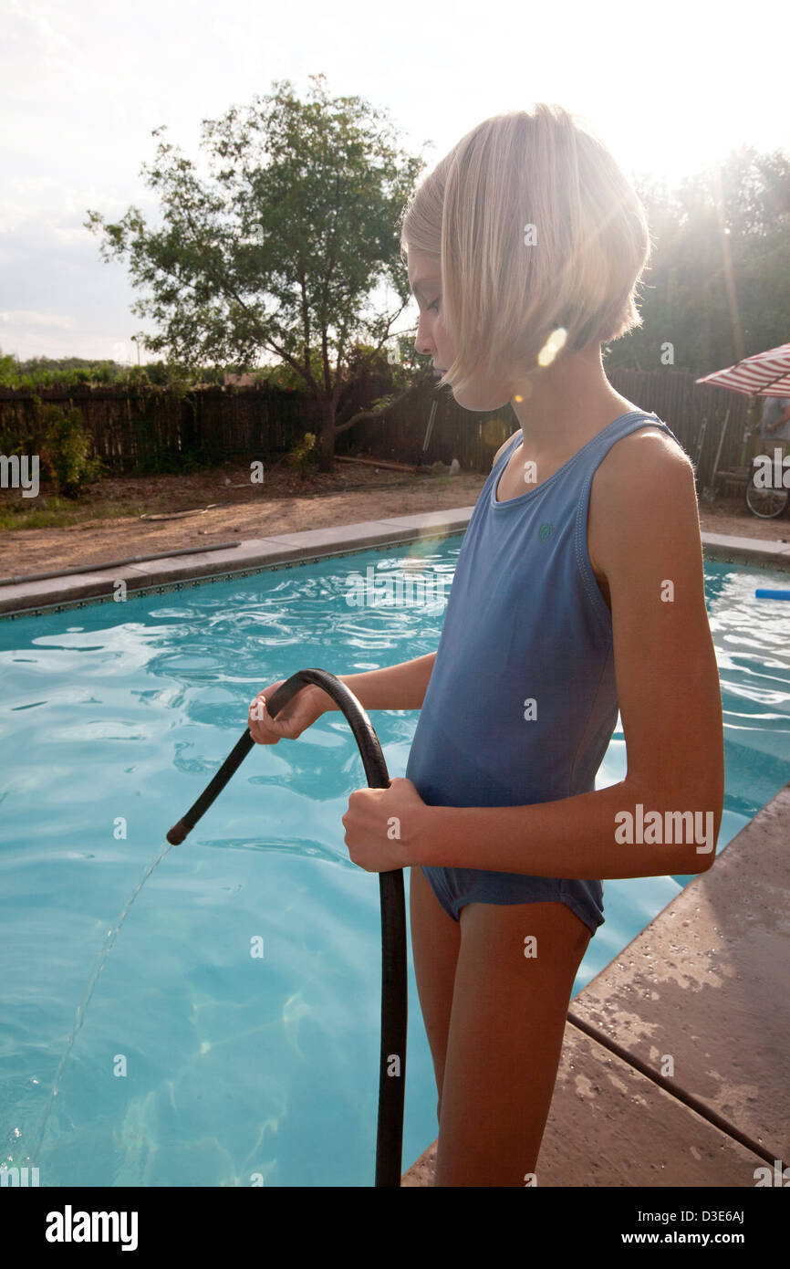 Dieci anni di vecchia ragazza versare acqua in una piscina da un tubo flessibile. Immagini Stock