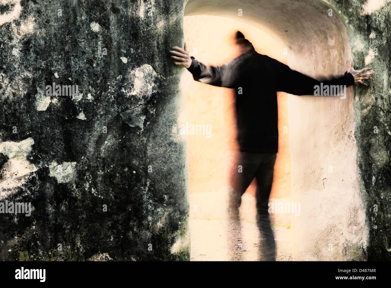 Adulto maschio muovendosi da tenebre in luce attraverso il portale. Egli è in possesso al muro di pietra. Immagini Stock