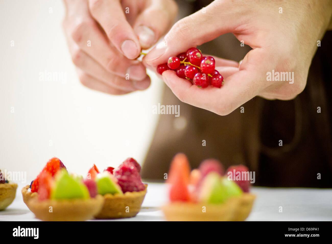 Baker rendendo crostate di frutta in cucina Immagini Stock
