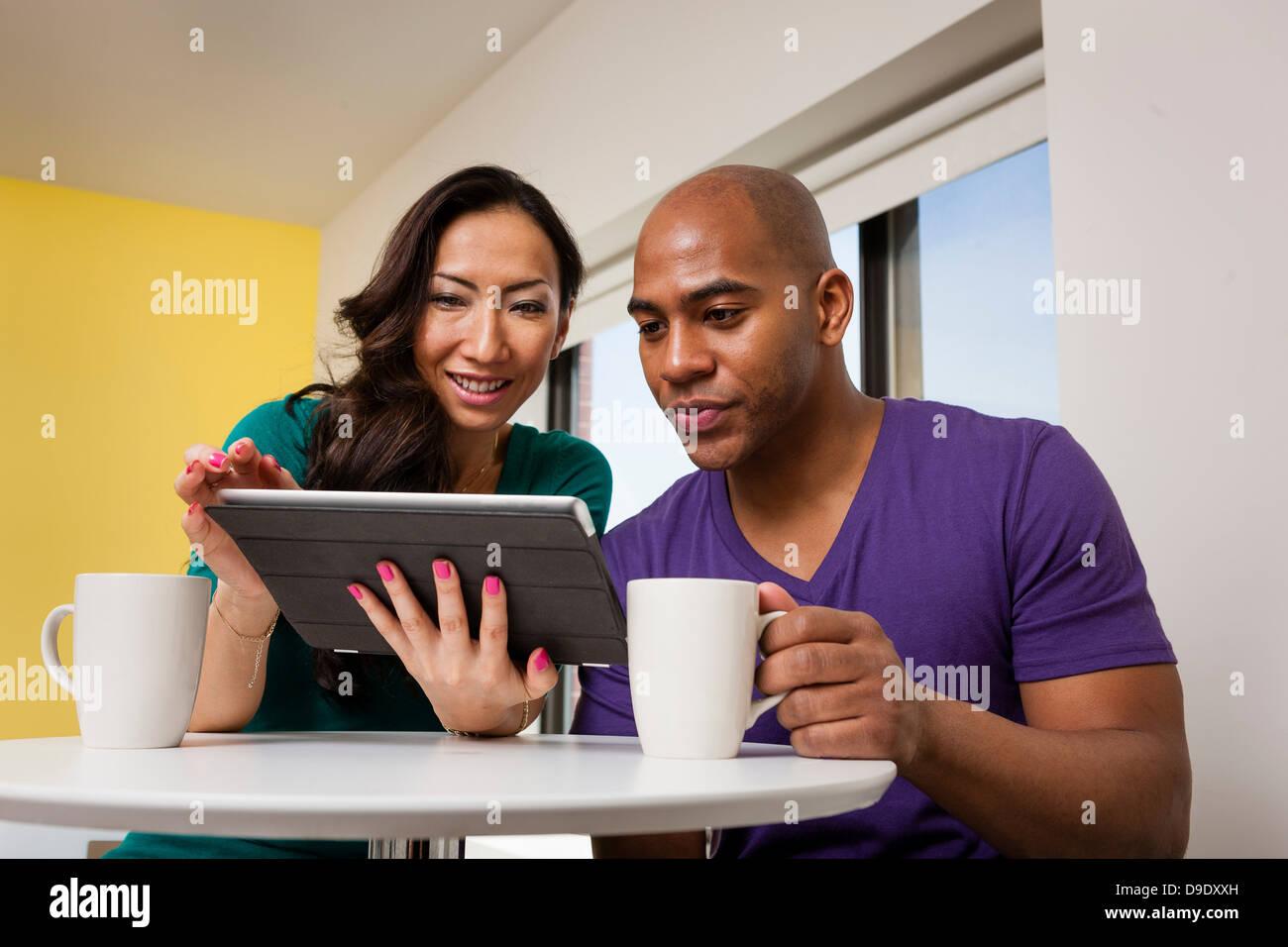 Metà adulto giovane guardando a tavoletta digitale e di bere il caffè Immagini Stock