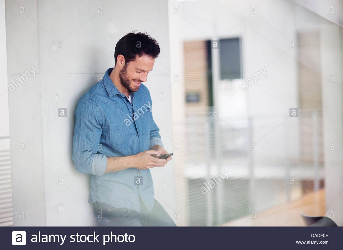 Uomo che guarda in basso al telefono cellulare Immagini Stock