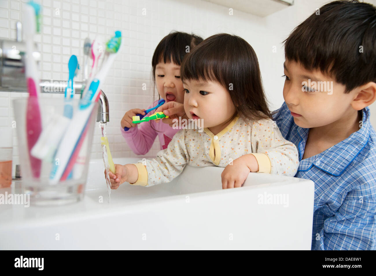 Fratello aiutare le sorelle a pulire i denti Immagini Stock