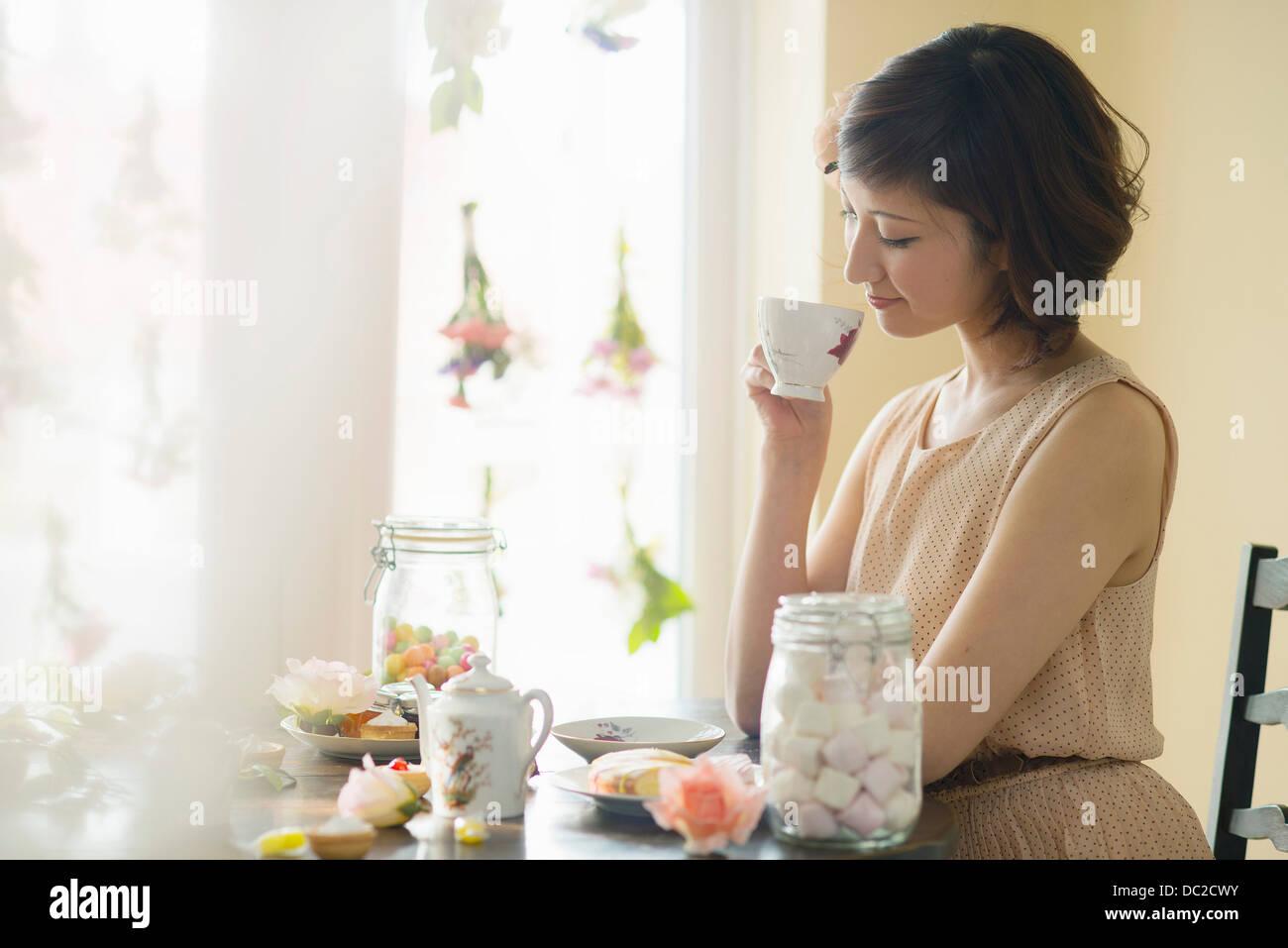 Donna che guarda in basso a tazza da tè Immagini Stock