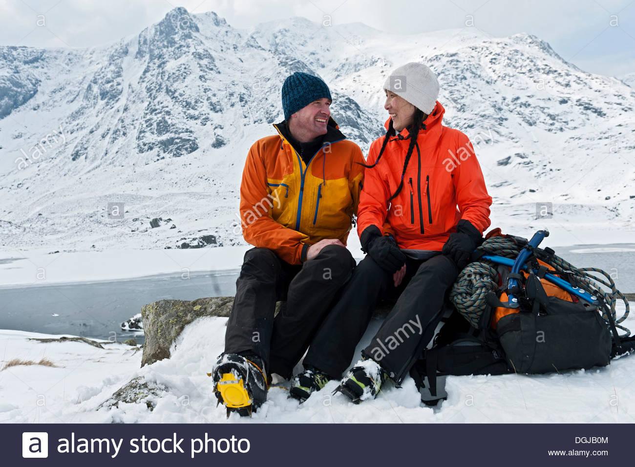 Alpinismo giovane prendendo una pausa di fronte montagne coperte di neve, Devils Kitchen, llyn Idwal, Cwm Idwal, Immagini Stock