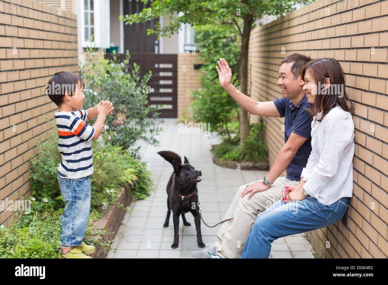 Famiglia con cane, padre sventolare al figlio Immagini Stock