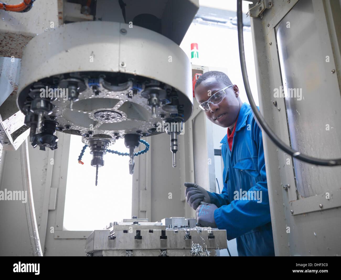 Apprendista ingegnere utilizzando CNC (computer a controllo numerico tornio) in fabbrica, ritratto Immagini Stock