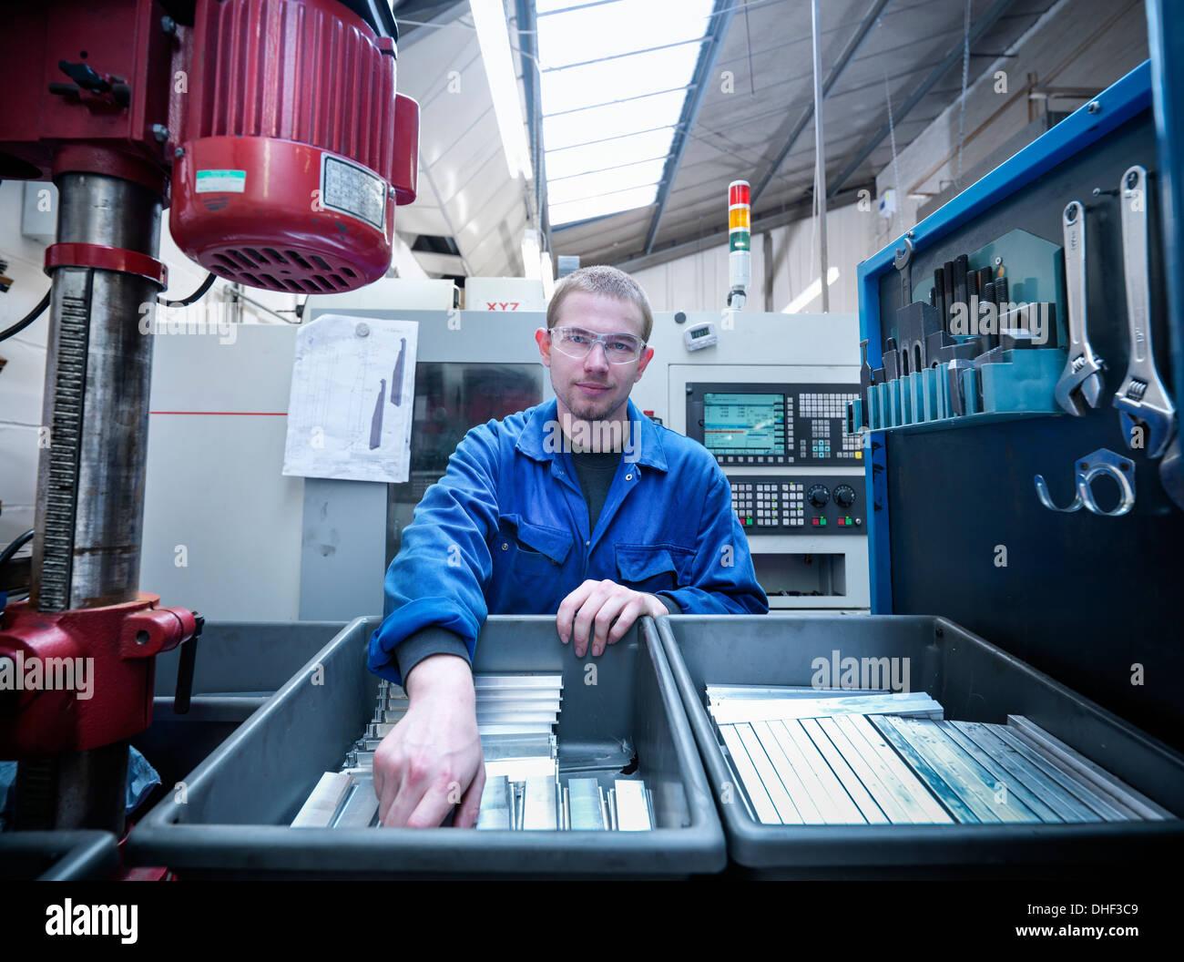 Apprendista ingegnere con componenti in fabbrica, ritratto Immagini Stock