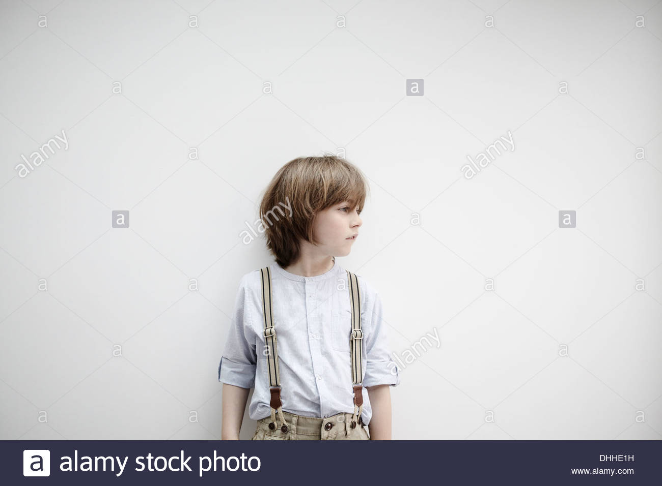 Ragazzo in piedi contro il muro bianco Immagini Stock